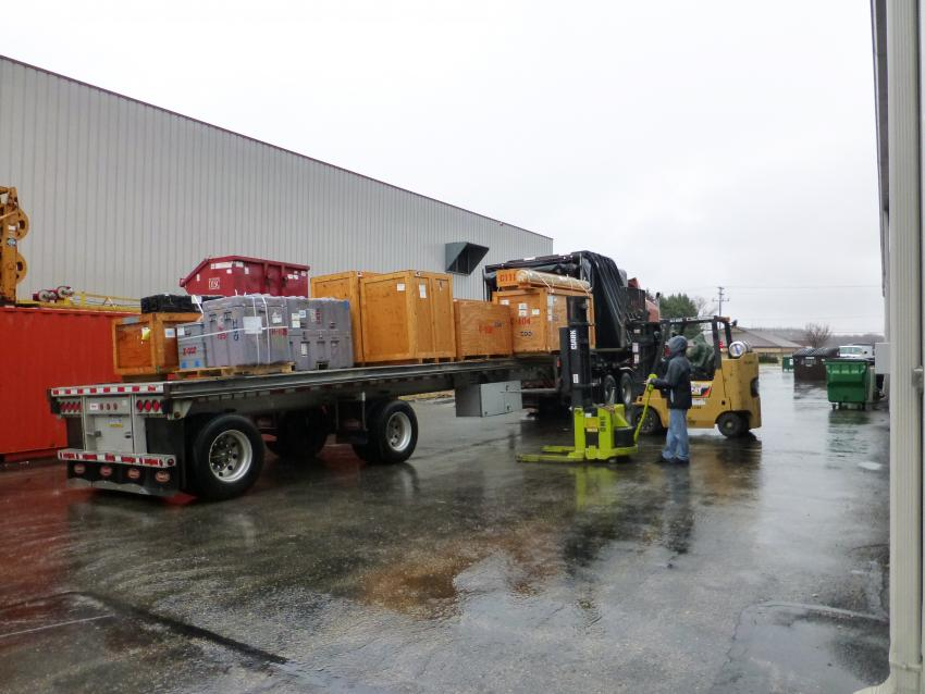 IDP engineers Josh Goetz and Jay Johnson unload a flatbed truck full of drilling equipment