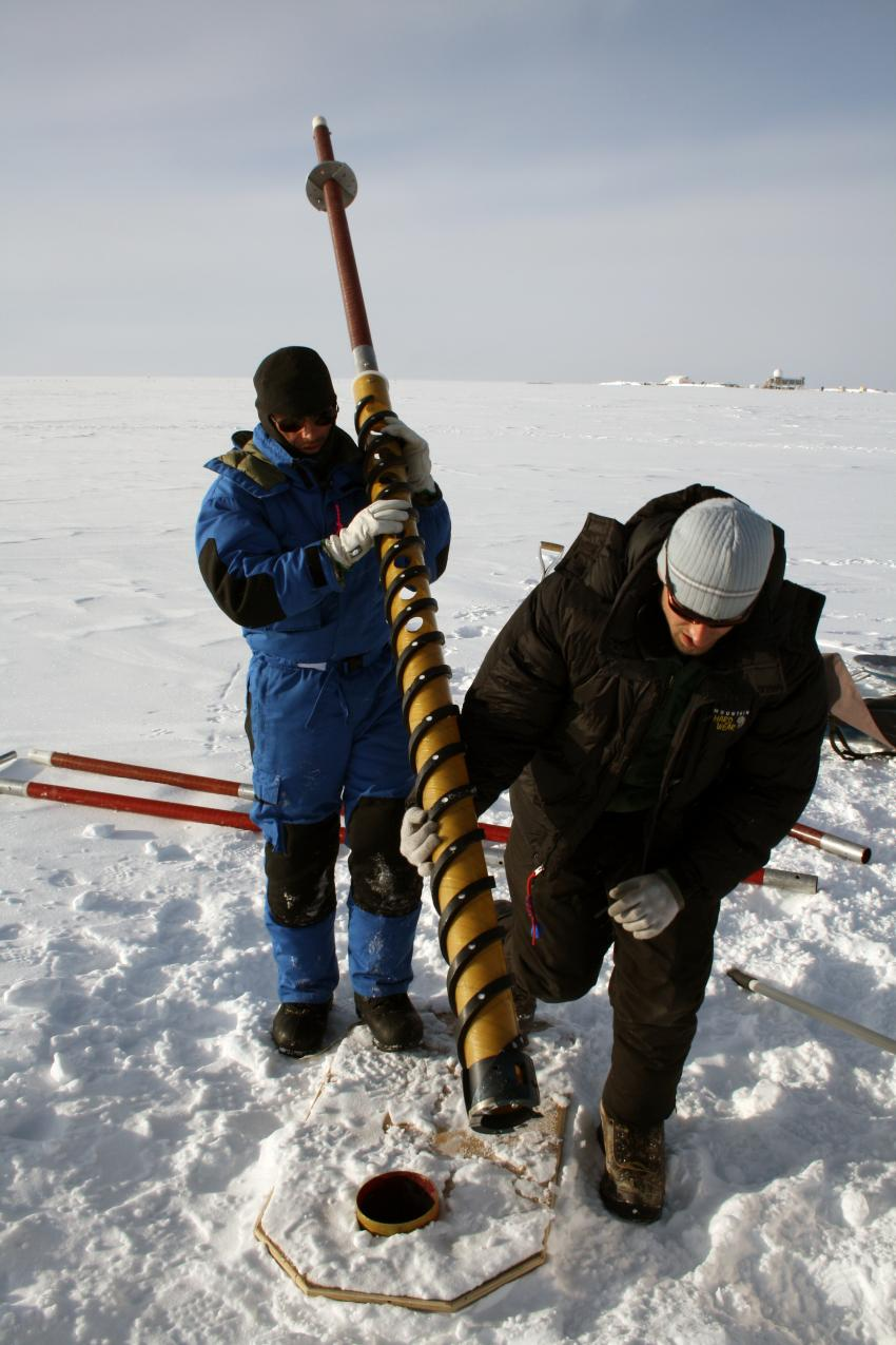 A scientist operates a PICO hand auger outside of Summit Station, Greenland