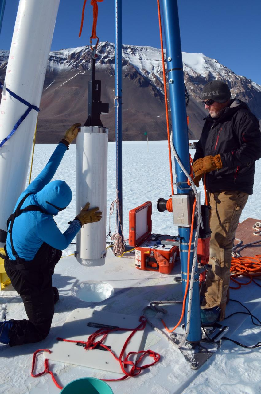 Scientist Michael Dyonisius, foreground, assists IDP driller Mike Jayred with drilling an ice core on Taylor Glacier, Antarctica
