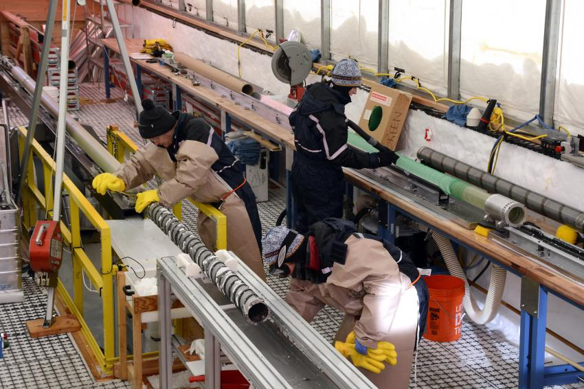 Science team members work in the South Pole Ice Core drill tent, cleaning the drill and measuring ice cores