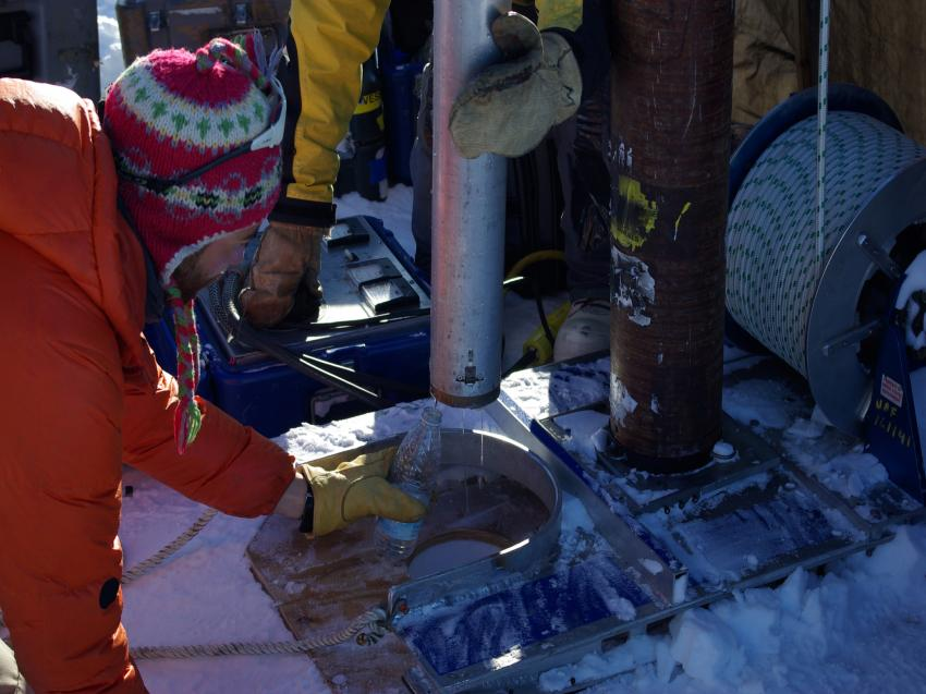 Collecting firn water from the drill head of the thermal drill during the 2013 field season in SE Greenland