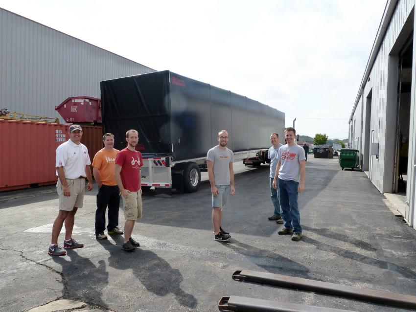 A happy IDDO team in front of the fully-loaded Conestoga trailer
