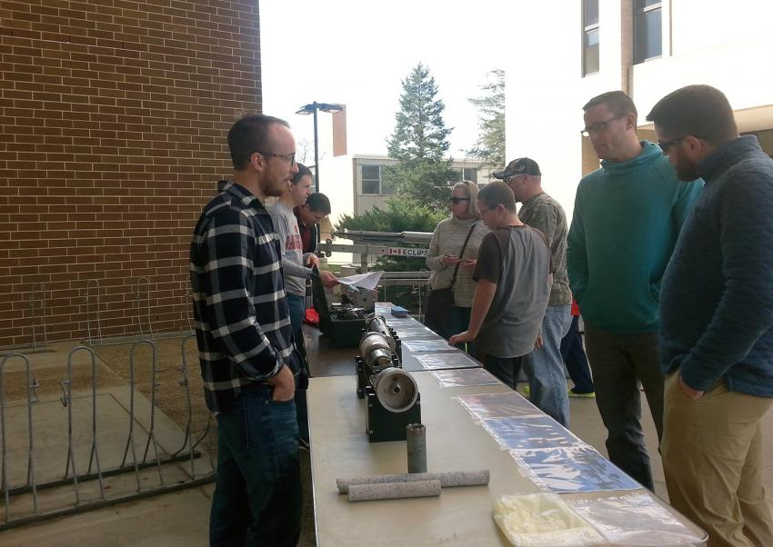 Visitors in Madison, WI observe drill parts and photos as engineers answer questions