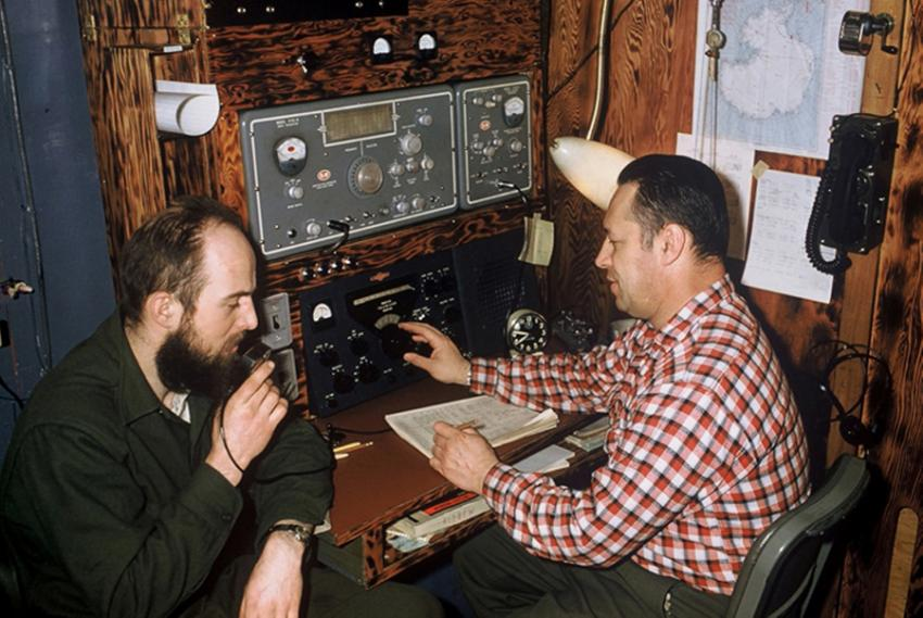 Charles Bentley, left, uses a ham radio while sitting next to station leader Steve Barnes at Byrd Station during his second winter of the International Geophysical Year