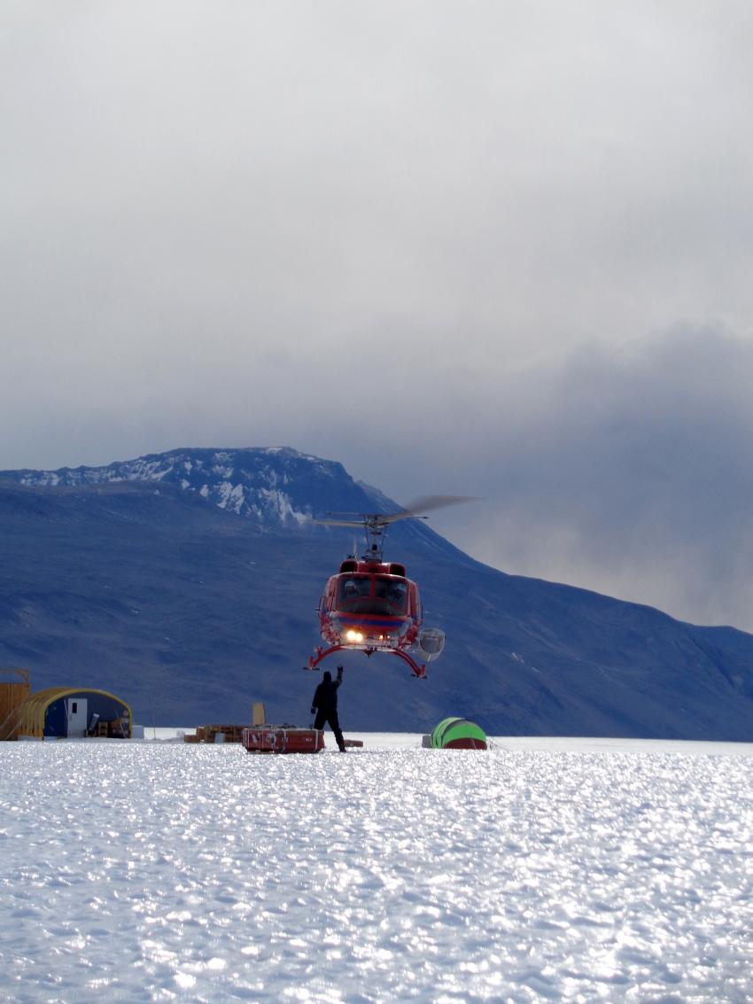 Driller Mike Jayred attaches Blue Ice Drill cargo to a waiting helicopter at Taylor Glacier, Antarctica