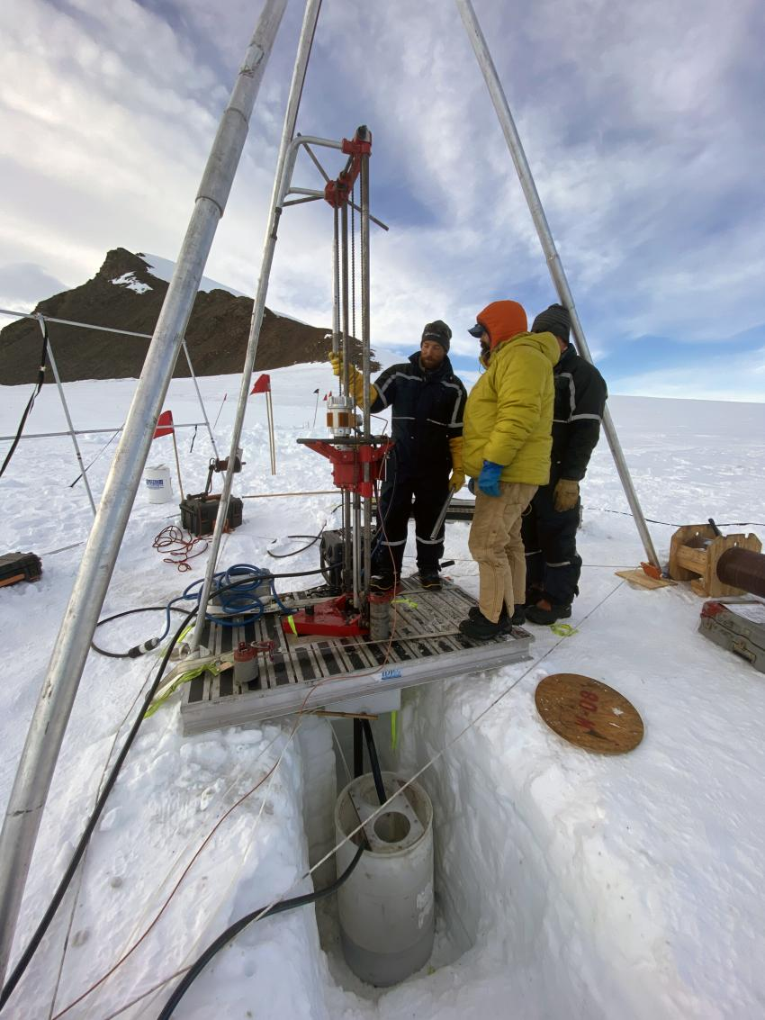 IDP Engineer Grant Boeckmann (left) operates the Winkie Drill on Thwaites Glacier in the Hudson Mountains. Also shown is scientist Seth Campbell (center) and IDP Research Intern Elliot Moravec (right)